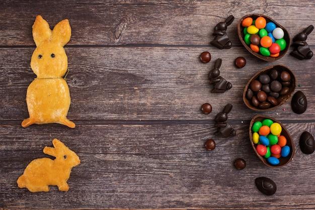 Płaska kompozycja z czekoladowymi pisankami, królikiem i słodyczami na ciemnym tle drewnianych. widok z góry. z miejscem na kopię