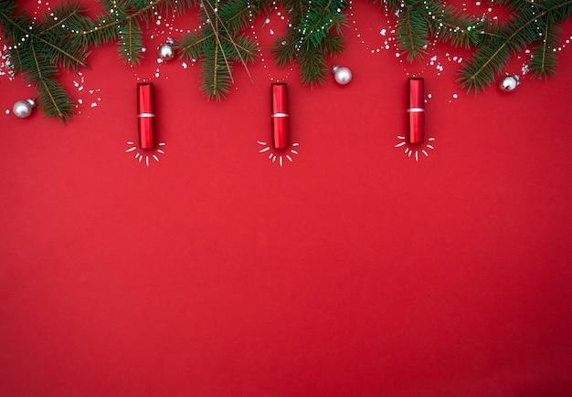 Płaska kompozycja z czerwoną szminką w postaci lampek choinkowych. widok z góry