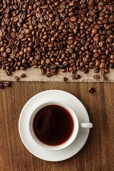 Płaska kompozycja z filiżanką gorącej kawy i ziaren kawy