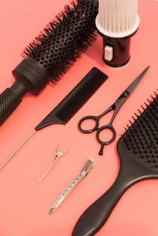 Płaska kompozycja z fryzjerskim zestawem na różowym stole. zestaw fryzjerski z narzędziami i wyposażeniem: nożyczki, grzebienie i spinki do włosów. salon fryzjerski i salon piękności