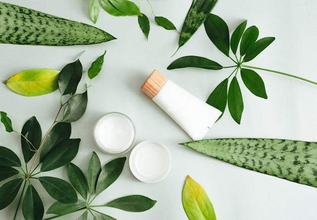 Płaska kompozycja z kosmetykami. naturalne kosmetyki i zielone liście