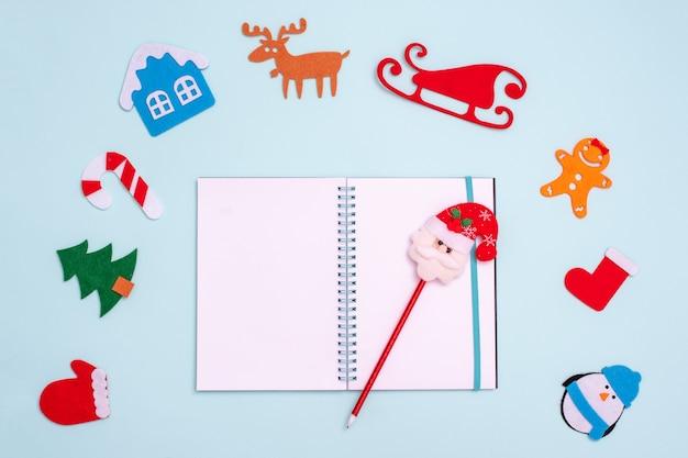 Płaska kompozycja z pustym, otwartym długopisem ze świętym mikołajem i zabawkami świątecznymi rękawiczka pingwin jodłowy domek z jelenia sanie piernikowa skarpeta