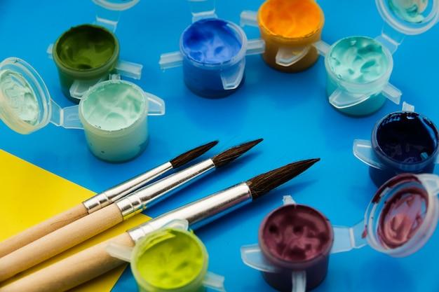 Płaska kompozycja z różnymi farbami akrylowymi lub olejnymi i pędzlami