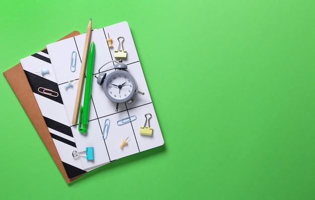 Płaska kompozycja zeszytów, ołówka, długopisu, segregatorów, budzika na zielono.
