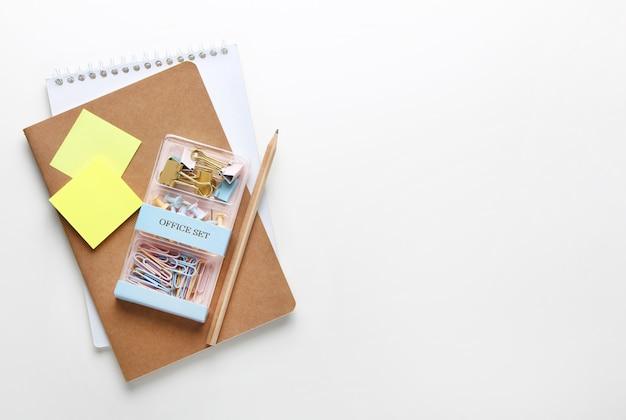 Płaska kompozycja zeszytów, ołówków, segregatorów. widok z góry na różne artykuły papiernicze na biurku.