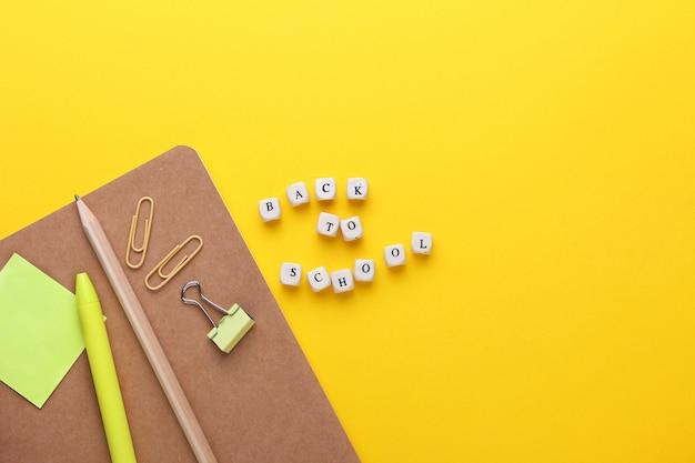 Płaska kompozycja zeszytu, ołówka, długopisu, segregatorów.