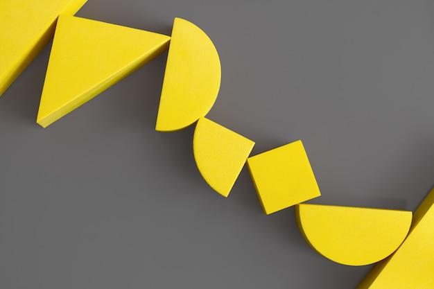 Płaska kompozycja żółtych geometrycznych kształtów na ostatecznej szarej powierzchni. kolory roku 2021. rozświetlająca i ostateczna szarość. koncepcja minimalizmu.