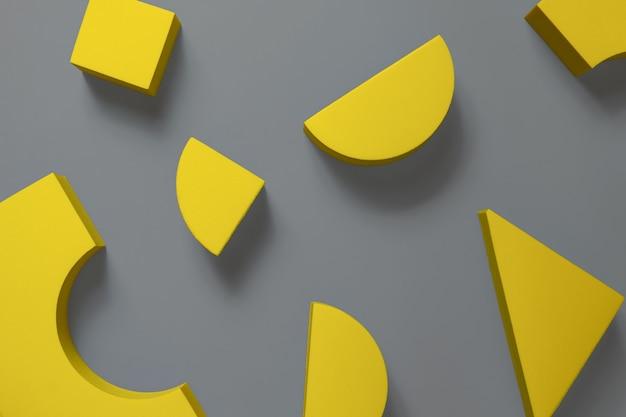 Płaska kompozycja żółtych geometrycznych kształtów na ostatecznej szarej powierzchni. kolory roku 2021