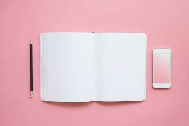 Płaska konstrukcja biurka workspace z pustym ołówkiem notebooka i telefonu komórkowego na różowym tle vintage pastelowy kolor tła.