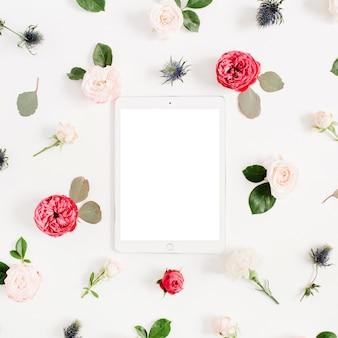 Płaska kwiatowa ramka z tabletką, czerwonymi i beżowymi pąkami kwiatów róży na białym tle
