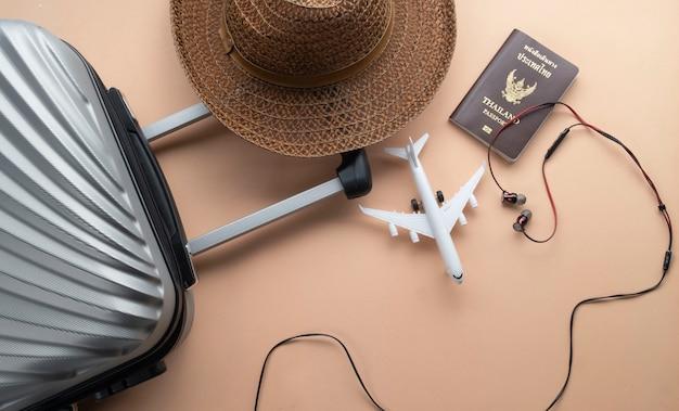 Płaska leżąca szara walizka z brązowym kapeluszem i mini samolotem