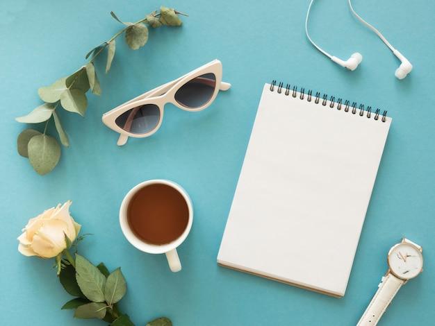 Płaska makieta kobiecego notatnika do zrobienia. herbata, kwiaty i słuchawki na niebieskim tle.