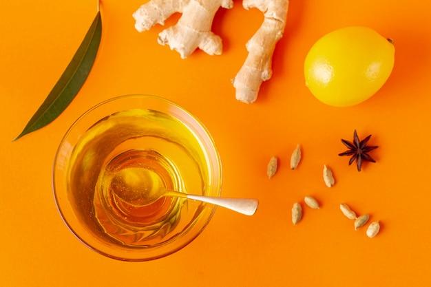 Płaska miska imbiru z cytryną i miodem z łyżeczką