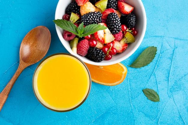 Płaska miska świeżych jagód i owoców z sokiem