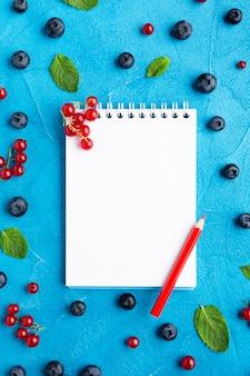 Płaska miska świeżych jagód z notatnikiem