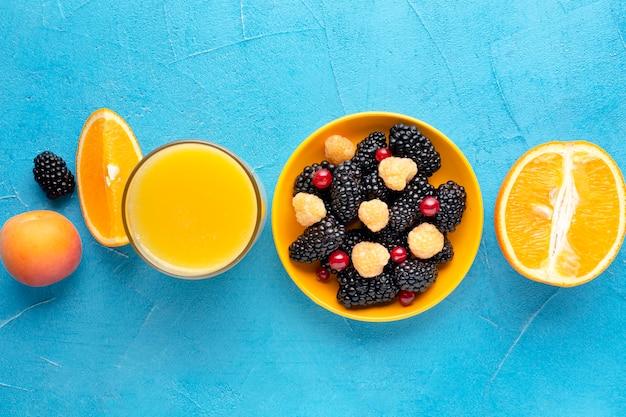 Płaska miska świeżych jagód z sokiem i pomarańczami