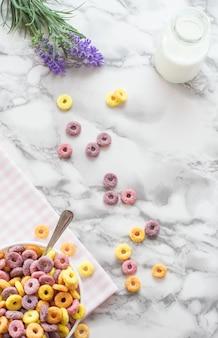 Płaska miska z kolorowymi płatkami śniadaniowymi.