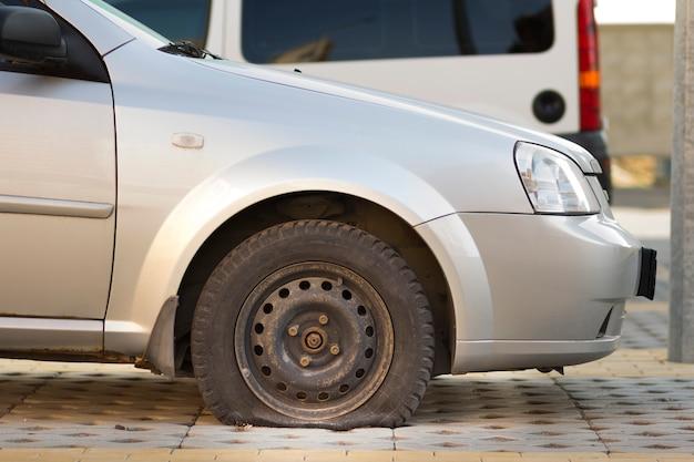 Płaska opona samochodu na chodniku. boczny widok outdoors pojazdu zakończenie up. problem z transportem, pojęcie wypadku i ubezpieczenia.