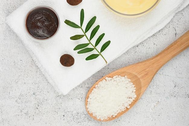 Płaska pielęgnacja skóry. płaski układ z akcesoriami, kosmetykami spa, solą do kąpieli, kremem i ręcznikami. produkt do pielęgnacji skóry, naturalny kosmetyk, płaski obraz.