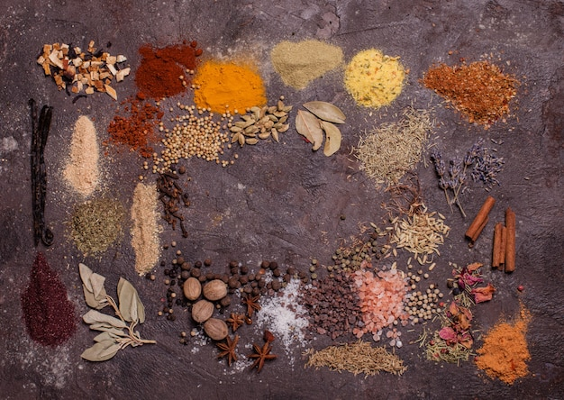 Płaska rama kompozycji świeckich z różnych przypraw na brązowym tle łupków, widok z góry
