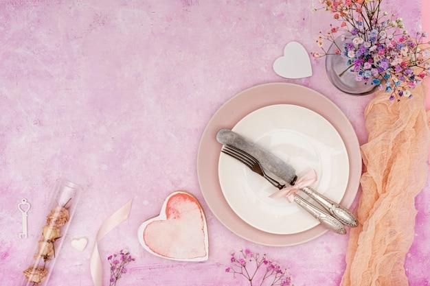 Płaska rama leżała z talerzem i sztućcami na różowym tle