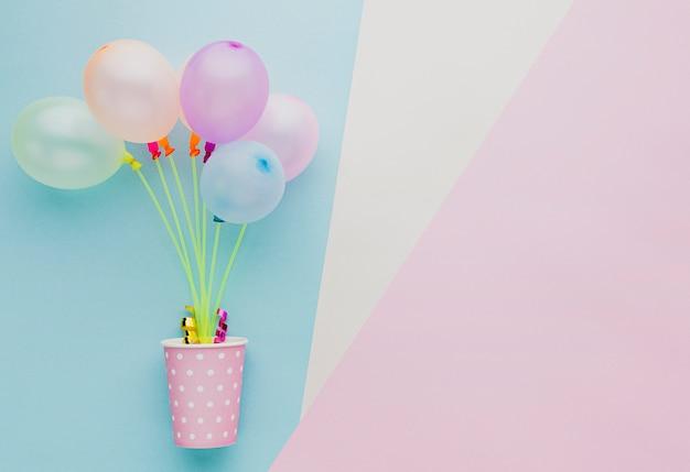 Płaska rama z kolorowymi balonami i filiżanką