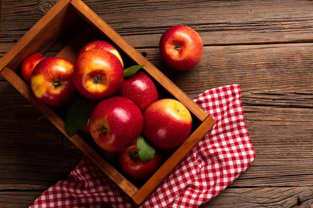 Płaska skrzynka z dojrzałymi jabłkami na tkaninie
