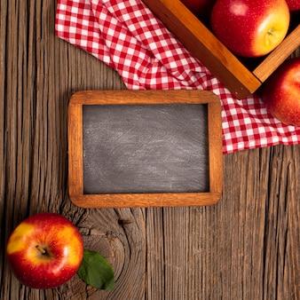 Płaska skrzynka z dojrzałymi jabłkami z tablicą