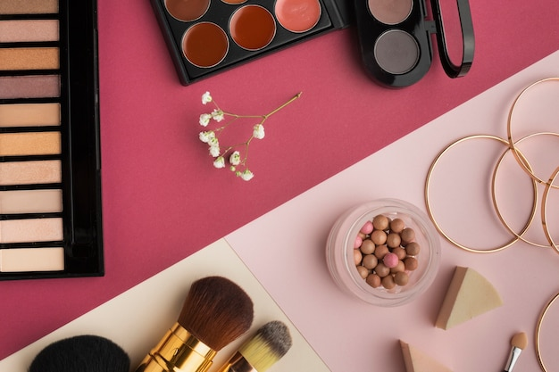 Płaska świecka dekoracja z kosmetykami i różowym tłem