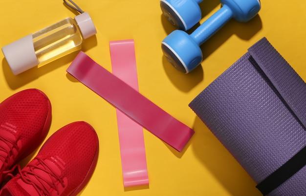 Płaska świecka kompozycja fitness. sprzęt sportowy na jasnożółtym tle z głębokim cieniem.