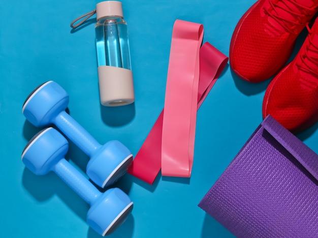 Płaska świecka kompozycja fitness. sprzęt sportowy na jasnym niebieskim tle z głębokim cieniem.