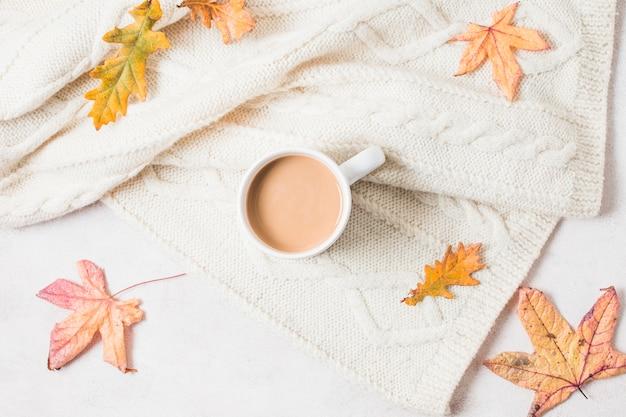 Płaska świeża filiżanka kawy na przytulnym swetrze