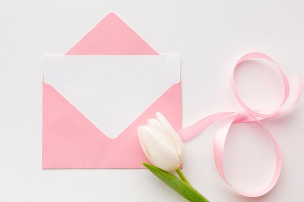 Płaska świeża kompozycja na dzień kobiet z różową kopertą