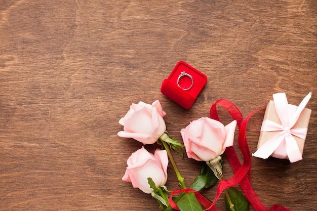 Płaska świeża kompozycja z różami i pierścionkiem zaręczynowym