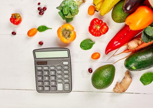 Płaska torba na zakupy papierowa z asortymentem świeżych warzyw i owoców oraz kalkulator, bio zdrowa, ekologiczna żywność na białym tle, styl super market, sklep spożywczy, dieta wegetariańska.