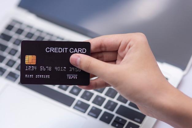 Płaski człowiek świecki za pomocą karty kredytowej do zakupów online na tle klawiatury komputera