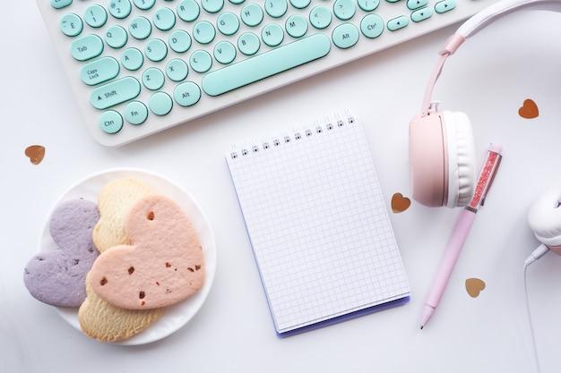 Płaski długopis, otwarty notatnik, talerz z ciasteczkami w kształcie serca