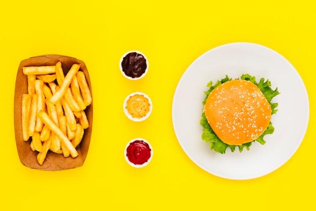Płaski hamburger z frytkami i sosami