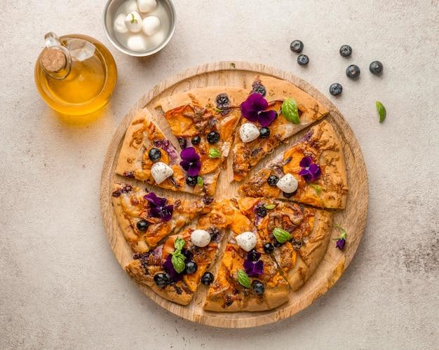 Płaski kawałek pysznej pizzy z jagodami i płatkami kwiatów