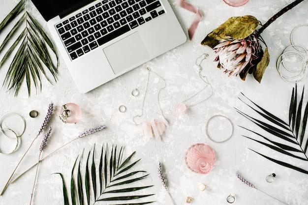 Płaski, kobiecy obszar roboczy do domowego biura z laptopem, kwiatem proteus, naszyjnikiem, gałązkami palmowymi i akcesoriami