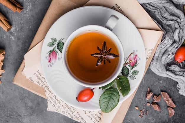 Płaski kubek z herbatą, anyżem i cynamonem