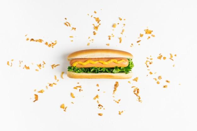 Płaski leżący hot-dog z chrupiącą cebulą kruszy się