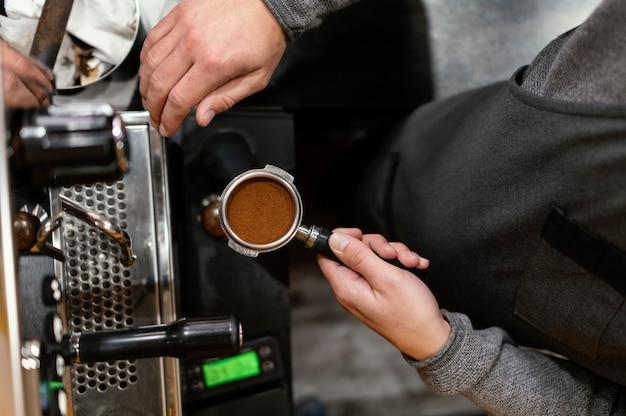 Płaski leżał męski barista trzymając kubek profesjonalnego ekspresu do kawy