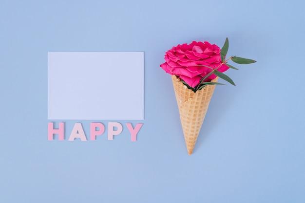 Płaski leżał stożek lodów z różową różą na niebiesko-białym czystym pustym miejscu. szczęśliwy tekst