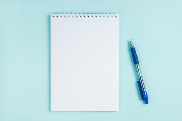 Płaski notatnik i długopis na stole na niebieskim tle. makieta