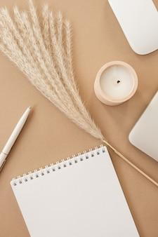Płaski notatnik z klapką i pustą kartką papieru. laptop, trawa pampasowa, artykuły papiernicze na stole w beżowym brzoskwiniowym pastelowym tle.