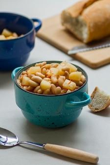 Płaski posiłek z fasolą i ziemniakami w małym garnku