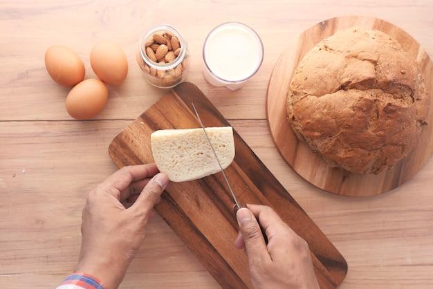 Płaski skład ręki człowieka do krojenia sera na desce do krojenia