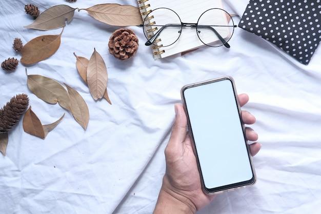 Płaski skład trzyma mądrze telefon na białym tle ręka
