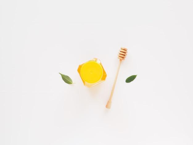 Płaski słoik miodu z łyżką i liśćmi koncepcja żywności bio